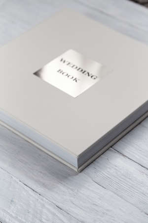 Photo album on a white wooden background. Photo album of white color with a leather cover and a metal inscription.
