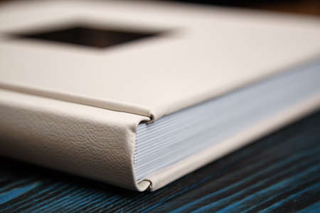 Photo album on a blue background. Photoalbum of white color with a leather cover and a metal inscription.