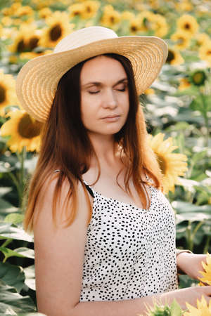 girl with hat, walking on the field of sunflowers, smiling beautiful smile, cheerful girl, style, lifestyle, ideal for advertising and photo the sun is shining bright and juicy Reklamní fotografie