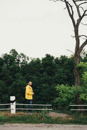a man in a yellow raincoat with a camera, against a background of rocks