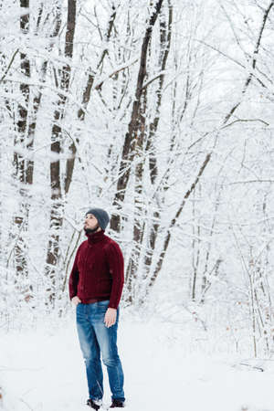 guy in a red knitted sweater and jeans holding a phone, standing on the snow in the winter forest