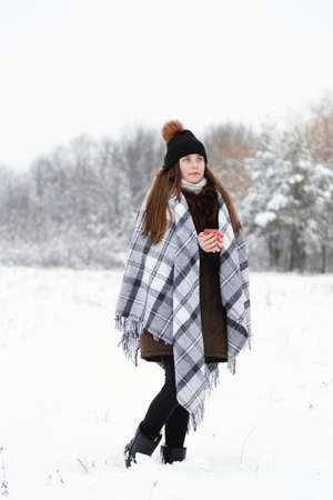 Portrait of a girl in the winter with a candle, in a checkered rug, full height