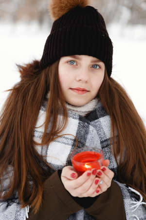 Portrait of a girl in the winter with a candle in a checkered rug