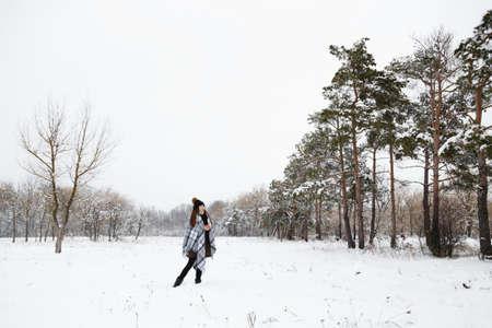 Portret dziewczynki zimą ze świecą, w kraciastym dywanie, pełna wysokość