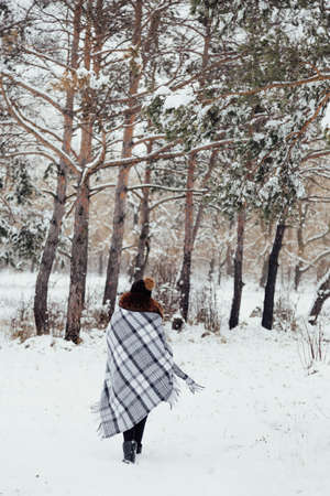 winter portrait of a girl wrapped in a checkered plaid
