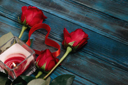 bouquet of red roses, a candle, a heart with a red ribbon on the old blue board Stockfoto