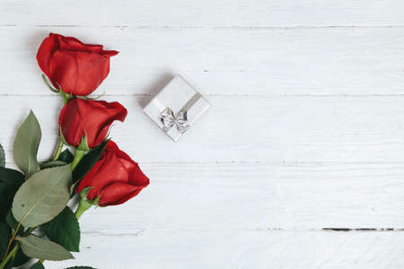 Red roses bouquet and gift box on white wooden background.