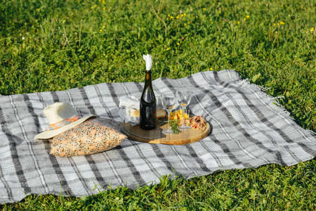 2 glasses of red wine with bread and cheese, pierced on a wooden tray.