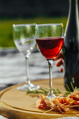 a picnic in nature a light meal under wine, on a wooden background two glasses of red wine, prosciutto Stockfoto