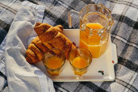 Tasty continental breakfast with fresh puff croissants, orange juice, closeup on croissants