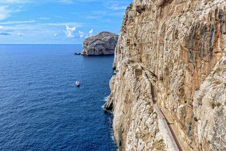 Boat rock wall path Grotta di Nettuno Sardinia Archivio Fotografico