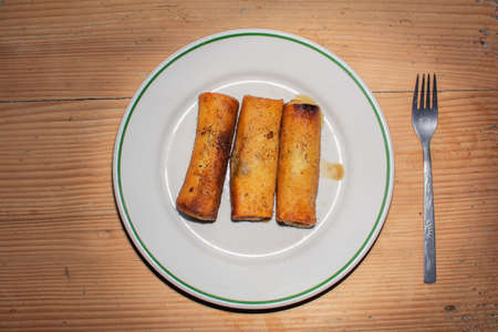 three croquettes on a plate on a wooden table Archivio Fotografico