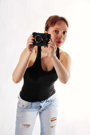 Beautiful woman with an old film camera on a white background.