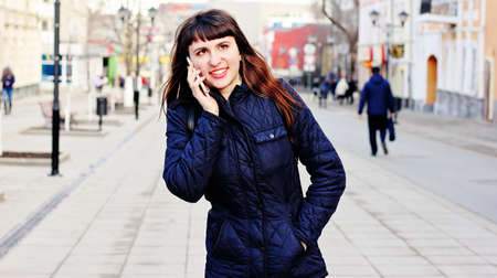 mobilephones: Young beautiful girl is talking on a mobile phone in the central city street.