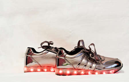 Original female sneakers with glowing soles isolated white background.