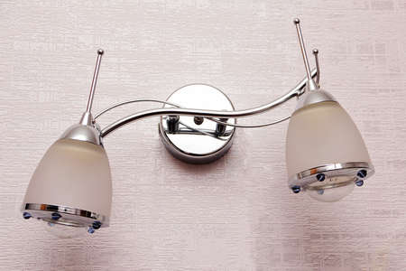 Wall sconce hanging on the wall of a city apartment. Stock Photo