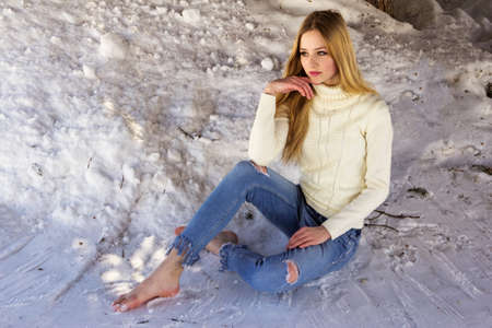 Cute beautiful teen girl sitting on snow barefoot in ripped jeans.