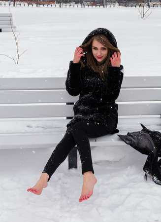 A beautiful Russian woman with bare feet sits on a bench in the winter.