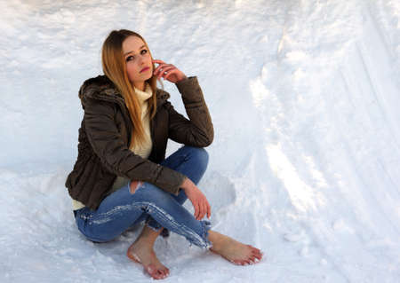 Pensive and sad barefoot girl with long blond hair sitting in the snow dreaming about something. Standard-Bild