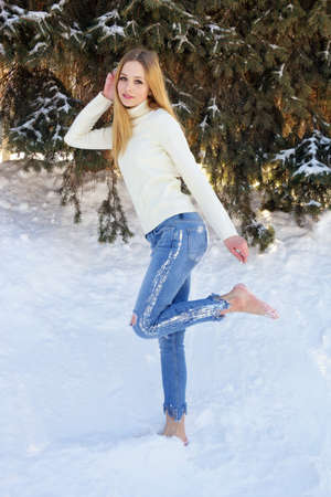 Cute beautiful teen girl posing barefoot in the snow in the Park.