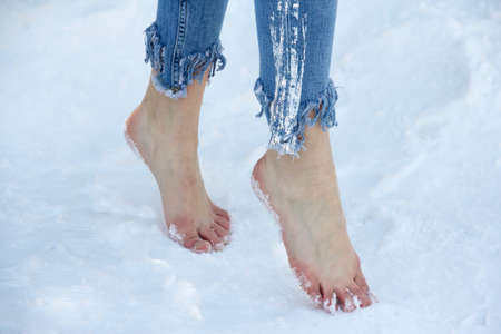 Slender beautiful girl feet close up in the snow.
