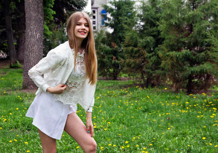 Cute and cheerful teen girl with long blonde hair posing in the Park.