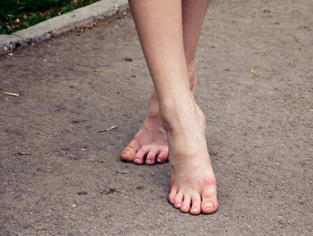 The feet of a girl walking on the pavement. Stockfoto