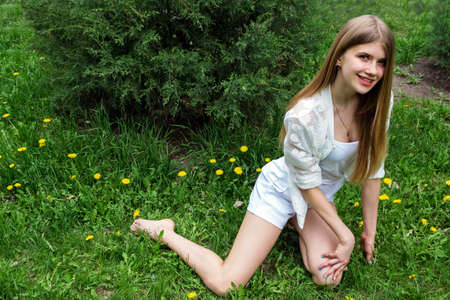 Cute smiling barefoot girl posing on the green lawn. Reklamní fotografie