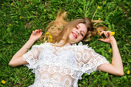 Cute girl with bliss lying on the green lawn.