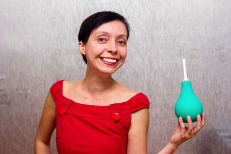 Smiling and happy woman holding an enema isolated by gray background.