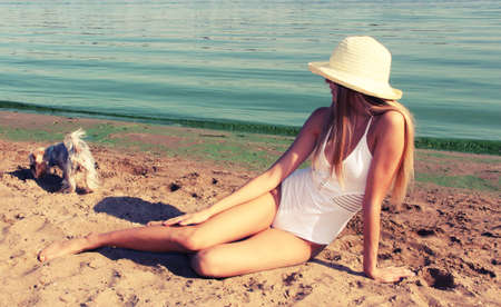 Girl on a sandy beach looking at a dog. Фото со стока