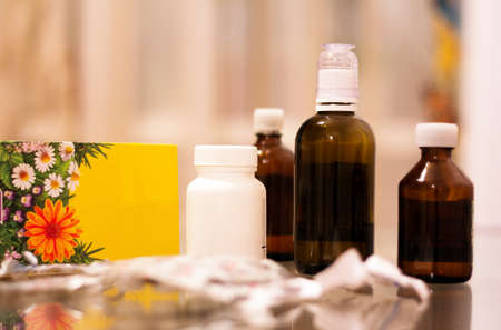 Bottles with medical drugs and medicinal herbs on the glass table.