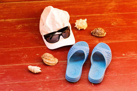 Summer beach holiday items and accessories on wooden surface.