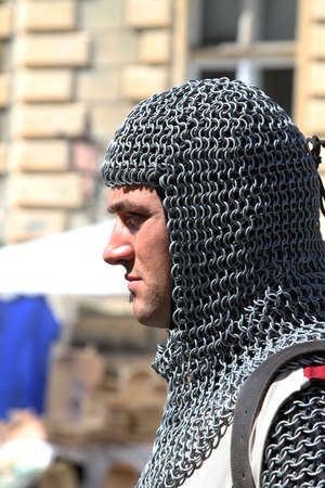 squire:  profile of squire with hood of mail against medieval buldings Stock Photo