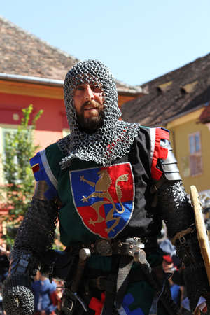 hauberk: men with beard posing as knight with coat of arms and swords against medieval buldings and blue sky Stock Photo