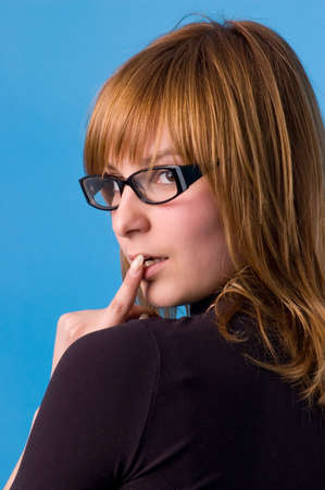 The girl on a blue background tries on glasses