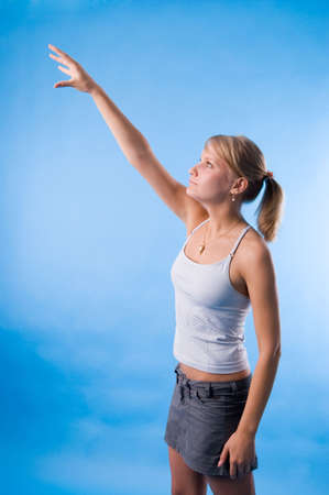 The girl in a white vest tries to reach the sky Stock Photo