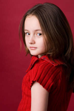 The girl of ten years in a red sweater in studio