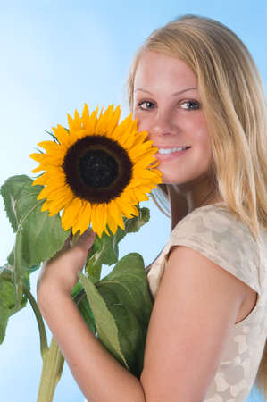 The attractive blonde in studio holds a sunflower in hands