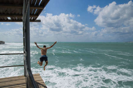 The guy jumps from a mooring in emerald waves.