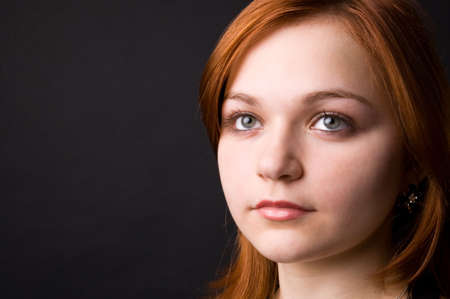 The charming young girl in studio on black background Stock Photo