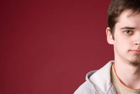 The young guy in studio on a red background