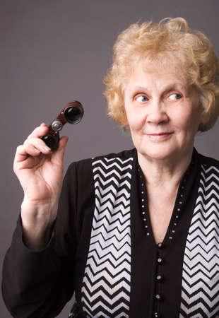 The cheerful elderly woman with binocular on a grey background.