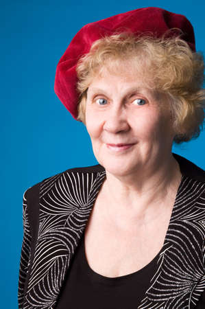 The cheerful elderly woman in red beret on a blue background. Stock Photo