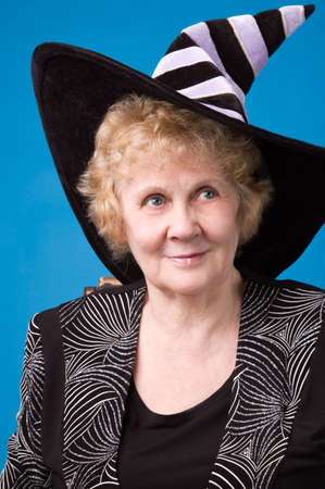The cheerful elderly woman in witchs hat on a blue background.