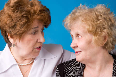 A portrait of two cheerful elderly women on a dark blue background.