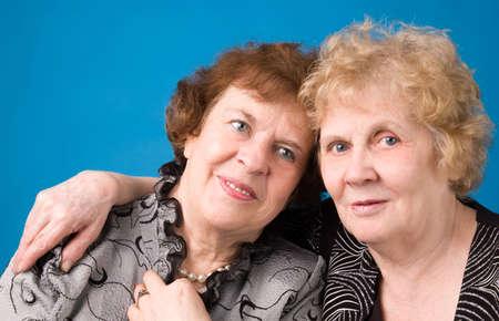 A portrait of two cheerful elderly women on a dark blue background.