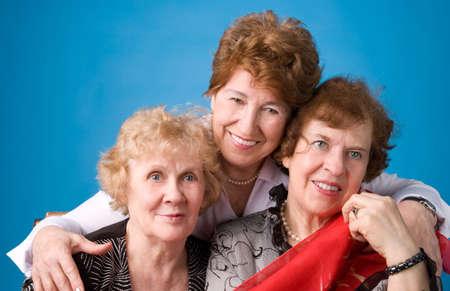 A portrait of three cheerful elderly women on a dark blue background.