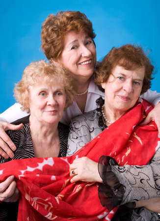 A portrait of three cheerful elderly women on a dark blue background.