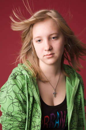The young girl in green clothes on a red background.